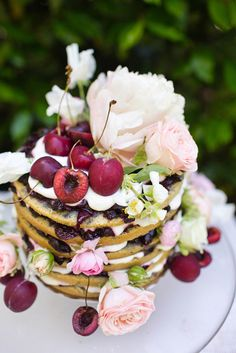 naked multi layer cake with cherries + pink flower decor