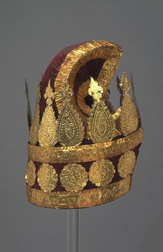 Items of dress of a Burmese minister, Konbaung Dynasty (1752-1885), consisting of a court costume of red velvet and gold and a white muslin jacket and headdress, ca. 1850 to 1885.