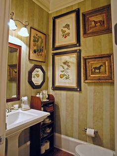 The green-striped walls of this bathroom are decorated with framed botanical prints.
