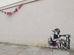 graffiti in london shows a boy sewing union jack bunting, a small reminder during celebrations of those who supply us with the souvenirs
