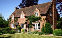 An English country cottage, brick built, complete with a manicured lawn and an abundance of plant life.