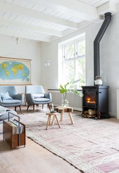 Finally, here's a fun exercise to show the range of style that the Scandinavian label encompasses, thanks to vtwonen. This is the first of three living rooms in a farmhouse, and it has classic Scandi elements: bare wood, white walls, wood-burning fireplace, wood stumps, and gray-blue furniture...