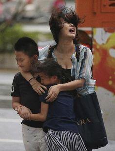 tifon en taiwan Una madre agarra a sus hijos ante una fuerte ráfaga de viento del tifón Soudelor en Taipei Taiwán el 7 de agosto de 2015. Foto AP Wally Santana