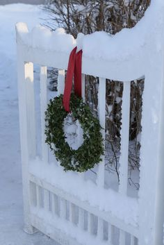Wreath hung on white picket fence. Simple and classy.