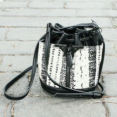 Danielle Nicole Mini Drawstring Bucket Bag Black Mini drawstring bucket bag. Black Matte hardware, digital snake print. Vegan Leather.  7 W x 7 H x 6 D 22  Adj. Strap Drop Danielle Nicole Bags