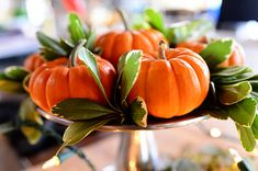 Simple pumpkins and leaves arranged on various heights of cake stands. To give them a little sparkle, some battery-operated light strings were thrown into the mix.