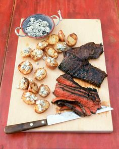In this meat-and-potatoes dish, everything is grilled at the same time; the steak is first marinated for added flavor, and the potatoes are boiled so they will be fluffy and tender inside their crisp grilled exteriors. Blue cheese is a classic steakhouse offering; place it on the potatoes as soon as they come off the grill, so the cheese will begin to melt.