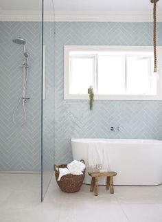 Herringbone tile pattern in light blue on modern bathroom wall.