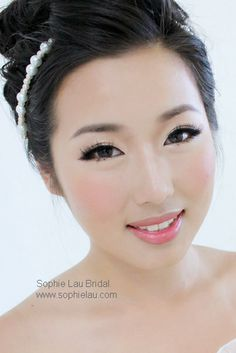 Clear skin, elongated winged eyes, faux lashes. Innocent, blushing bridal look.