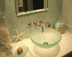 Love the color and texture of the natural elements against that glass tile and basin. So pretty. #Coastal #Bathroom