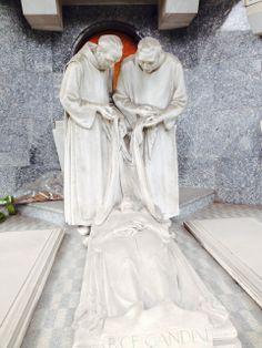 Scolpiti in marmo di Carrara due frati si apprestano a coprire con un sudario la salma della benefattrice Bice Bandini, che riposa oggi nell'edicola di famiglia