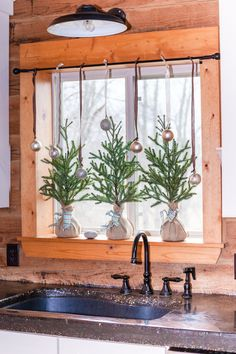 Mini Christmas trees wrapped in burlap for the kitchen window sill. Cozy cabin inspiration.