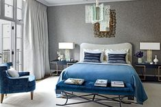 For a master bedroom in London, interior designer Jean Louis-Deniot opted for an inviting palette of blue and gray. Gray and white curtains, along with gray upholstered walls, enhance the various tones of blue in the room, including the bedding and luxe seating. #bluedesign #bluedecor #masterbedroom