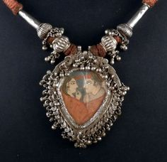 Extraordinary handpainted pendant in a yoni shape made with high grade silver from Rajasthan. The silver frame enhances the painting, representing a couple and protected by a glass.This pendand have been recently strung with cotton brown cord, but the pendant and the other silver beads are very old and quite worn. There are small silver bells all around the yoni pendant that makes a soft jingle when moving.
