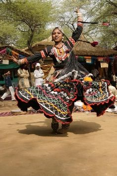 Delhi, India - February 12, 2009: Rajasthani dancer in ornate black costume trimmed with beads and sequins performing at the Sarujkund Fair near Delhi in India. photo
