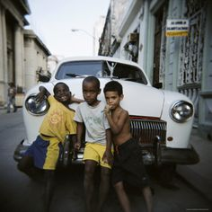 Three Young Boys Posing Against Old White American Car, Havana, Cuba, West Indies, Central America