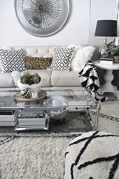 Beautiful Neutral and black and white living room with Beni Ourain rug, disco ball, gold, silver, leather sofa and leopard accent - Cuckoo4Design