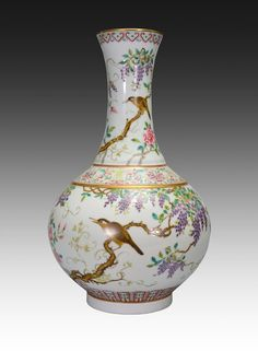 A LARGE OF FAMILLE ROSE BOTTLE VASE, Qing Dynasty. The bottle vase is pear-shaped. The exterior is decorated with birds chirpping while on a tree branch connected by different kinds of flowers, vines, and leaves. The vase is also decorated with imperial designs and Chinese characters. The bottom is decorated with Chinese characters. 15 1/2 in. tall.