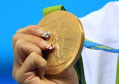 La mano de la española Mireia Belmonte sujetando la medalla de oro.