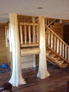 Two flared tree trunks used as newel posts on a log staircase.