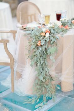 A rose and eucalyptus garland on a tulle covered sweetheart table for a spring wedding.