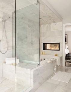 The shared wall between a master suite and the master bath is another great place for a dual fireplace. This bath was designed by none other than The Property Brothers. This page has some very useful information about home design and decor. Bathtub Remodel, Master Bath Remodel, Restroom Remodel, Shower Remodel, Modern Bathtub, Modern Bathroom, White Bathroom, Master Suite Bathroom, Zen Bathroom