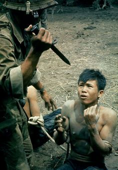 "Caption from LIFE. ""A captured Viet Cong kneels in terror as Vietnamese guard threatens him with bayonet. The guard demanded to know where arms were hidden. No reply. The guard let him go to a prison camp unharmed. In interrogating prisoners each side in the Vietnam war occasionally resorts to terror."" (Larry Burrows—Time & Life Pictures/Getty Images) See more: http://ti.me/Ot15KH"