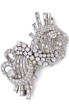 A diamond double-clip spray brooch, circa 1935 Each cluster of brilliant-cut diamonds issuing a spray of undulating lines set with baguette-cut diamonds, within a brilliant-cut diamond openwork surround of scrolling design, diamonds approx. 9.05cts total, length 6.7cm, fitted case by Asprey & Co. Ltd, New Bond Street, London