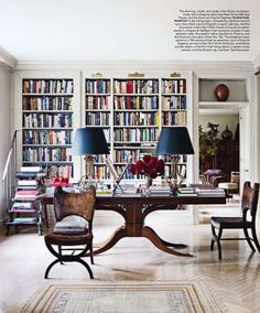 Library that could double as a dining room - love the two lamps on the pedestal table