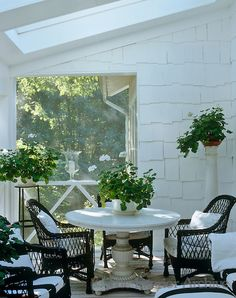 Black wicker chairs in this all-white garden room