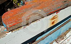 Colorful texture of Weathered Wooden Fishing Boat Rail with Rust Stains from Nail Holes; weathered red, white and blue paint visible on this ruined and beached vessel, which is in need of restoration.