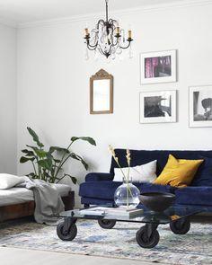 Mörkblå sammetssoffa i vardagsrum målat i vitt.