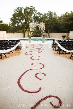This aisle decoration of rosebuds was such a beautiful touch for the wedding ceremony! As the night went on, the crushed rosebuds gave a gorgeous floral scent to the evening air.    #wedding #bride #inspiration #summer #roses #flowers #aisle runner #love #Hamilton Twelve venue #Austin #Texas, #austin wedding, #austin bride, #texas wedding, #texas bride