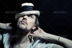 studio portrait of handsome young man in  white hat (background, beauty, black, caucasian, closeup, dark, elegance, european, face, facial, fashion, handsome guy, hat, head, human, look, male, man, men, model, one, person, photography, portrait, pose, shoulders, studio, style, tape, white)