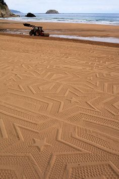 Artist Gunilla Klingberg prints patterns on the sand with a giant printer, created of a backhoe and a huge cylinder, on which the patterns are drawn with old truck tires… An installation on the Laga beach, for the Sense & Sustainability biennial in Spain.