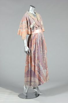 1978 Bridal Gown. A Zandra Rhodes Ayers Rock collection evening gown, 1978, labelled, the chiffon printed with Lace Mountain pattern in shades of peach, grey and lilac, with matching pink satin sash and a headband adorned with floret and shell shaped sequins