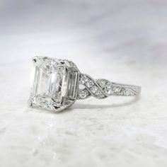 This extraordinary and rare heirloom diamond engagement ring from the swinging 30s will be the most unusual and gorgeous ring you have ever set your eyes on! I know for me, this ring is IT! It is very, very rare to find an authentic Art Deco engagement ring with an emerald cut diamond, especially an emerald cut diamond larger than 1 carat! So this glittering and fine 2.52ct I color, SI2 clarity diamond truly is a special find! Find similar authentic rings from other jewelers for almost…