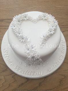 Gorgeous silver wedding anniversary cake decorated with simple white and silver daisies.