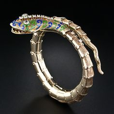 14K Gold and Enamel and Diamond Snake bracelet. A 'striking' snake bracelet superbly rendered in spring-loaded gold, blue and green enamel and sparkling round diamonds. The intricately constructed coiled body is composed of individually riveted textured gold sections leading to a wavy tail. A scintillating and sinewy serpent, circa 1960