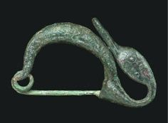 AN ETRUSCAN BRONZE FIBULA CIRCA LATE 6TH-5TH CENTURY B.C. With a plain arching bow, a coiled pin at one end, a catch-plate at the other extending into a stylized duck head curved back along the bow, with dotted circle eyes, the elongated bill flat on the underside