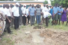 Dr Nii Kotei Dzani (bent), the Group CEO of Ideal Finance, cutting the sod for the commencement of a six-unit classroom block at the Ada Senior High School in the Greater Accra Region