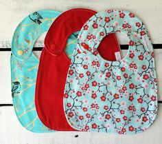 Beautiful baby girl bib set. This modern bib set would make a great complimentary gift to any red and teal or flower and bird themed nursery. Front is made of cotton and features red and teal Janpanese cherry blossoms and bird print. Back of bib is made of fleece for extra soft texture and style in complimentary white. Bibs have plastic snap closure that fits at the neck for baby or toddler and are oversized in width and length to protect the messiest little ones . These cotton and fleece…