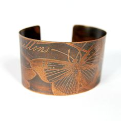 Stylish etched copper cuff bracelet with a selection of butterflies and a subtle lattice design in the background. One side says Papillions (French for butterflies) and the other side says Butterflies in a pretty script.     Piece has a black patina applied to bring out all the details and piece has been sealed to maintain color.