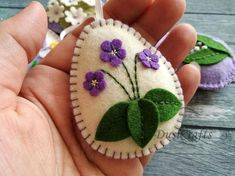Felt easter decoration - purple felt eggs with spring flowers including lily of the valley flowers, violet flowers, tulips, daffodils and hydrangea flowers. Listing is for 6 ornaments: - Lily of the valley on lavender lilac background - Daffodil on lavender lilac background - Tiny flowers