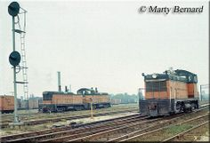 Milwaukee Road NW2 #672 runs light through the yard at Chicago's Western Avenue while a TR2 set, #696A/696B, roll past on a muggy September ...