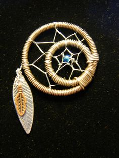 This is a one of a kind, wire wrapped, dream catcher pendant. Handmade with different color and gauged wire. Each paired with a glass bead and metal feather beads creating a twist on the traditional Native American version.