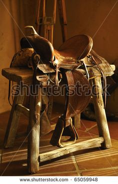 Authentic leather western cowboy saddle sitting on rustic wooden rack.