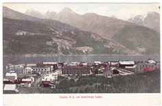 BC – KASLO, View of Town, Kootenay Lake and Passing Sternwheeler c.1900s PPC