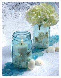 Blue mason jars can make beach wedding centerpieces something special. Prop ideas like seashells, coconuts, colored rocks and bamboo each give them a different style.