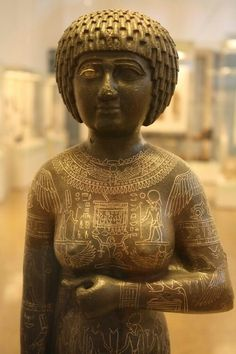 Copper alloy with precious metal inlay statue of Egyptian priestess Takushit.25th Dynasty c.a. 670 B.C.Found near Alexandria,Egypt.Takushit was the daughter of Akanuasa,a ruler during the reign of the Pharaoh Pianhi.